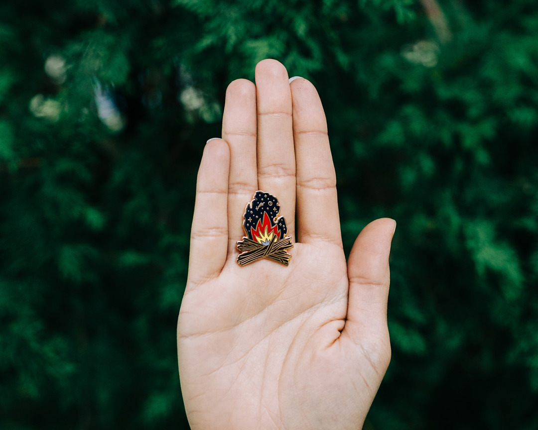 michigan campfire enamel pin held in palm of a hand