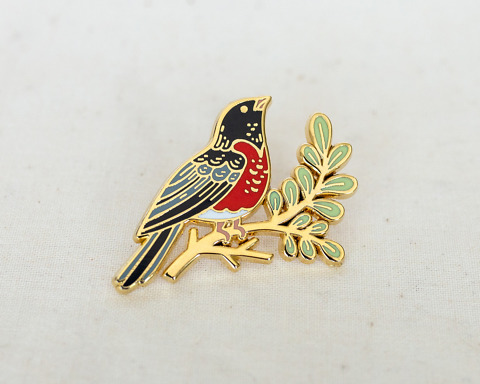 an enamel pin of a robin on a leafy branch in gold metal