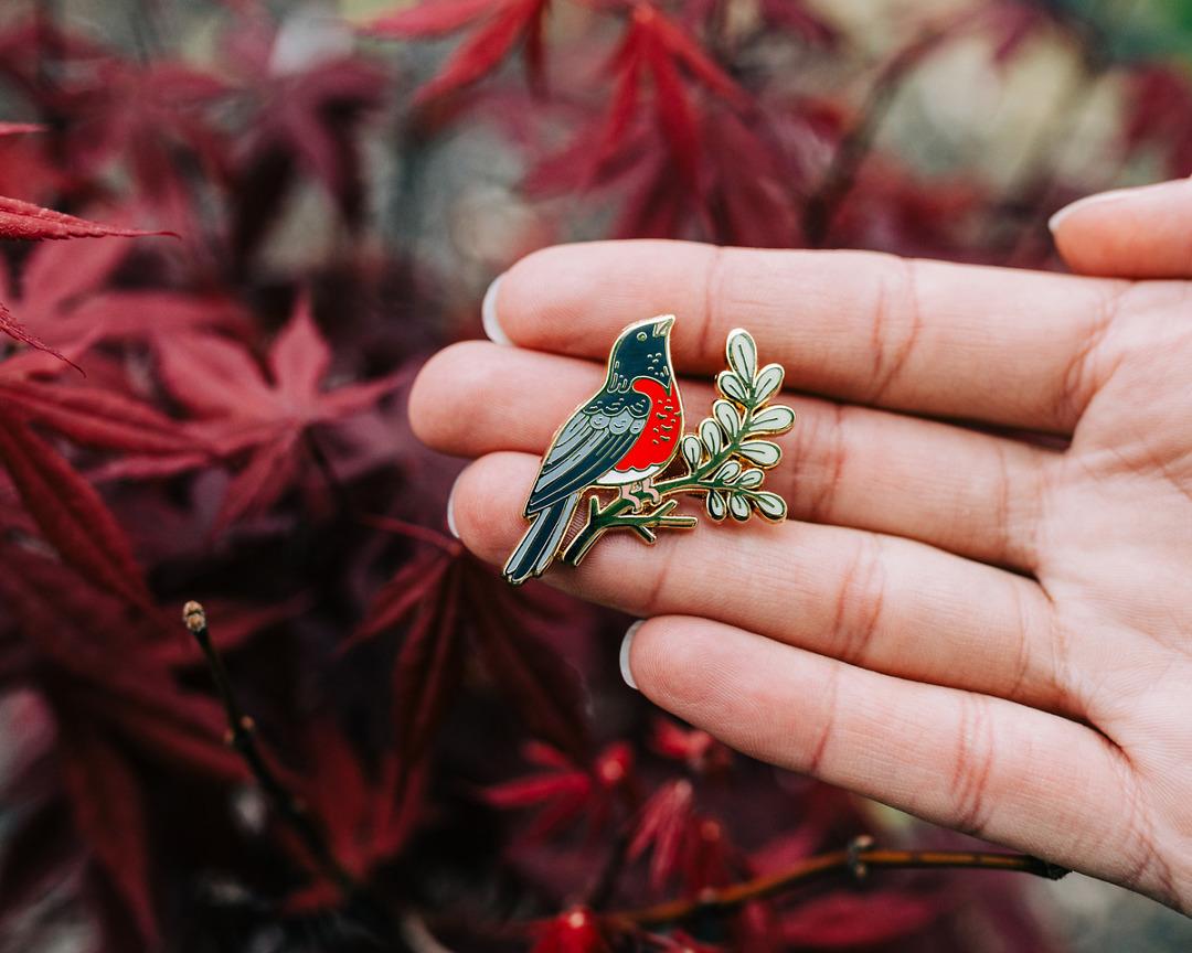 robin enamel pin held in hand against red leaves