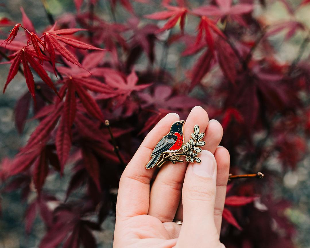 robin enamel pin being held in hand outdoors