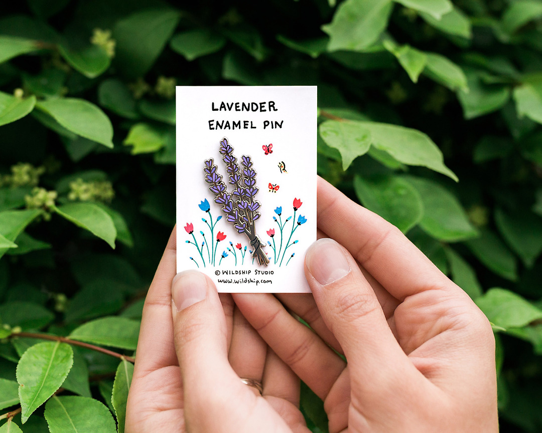 silver lavender enamel pin held by two hands in packaging by wildship studio