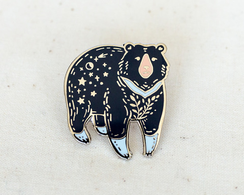 a silvery moon bear enamel pin with stars and moon on its rump