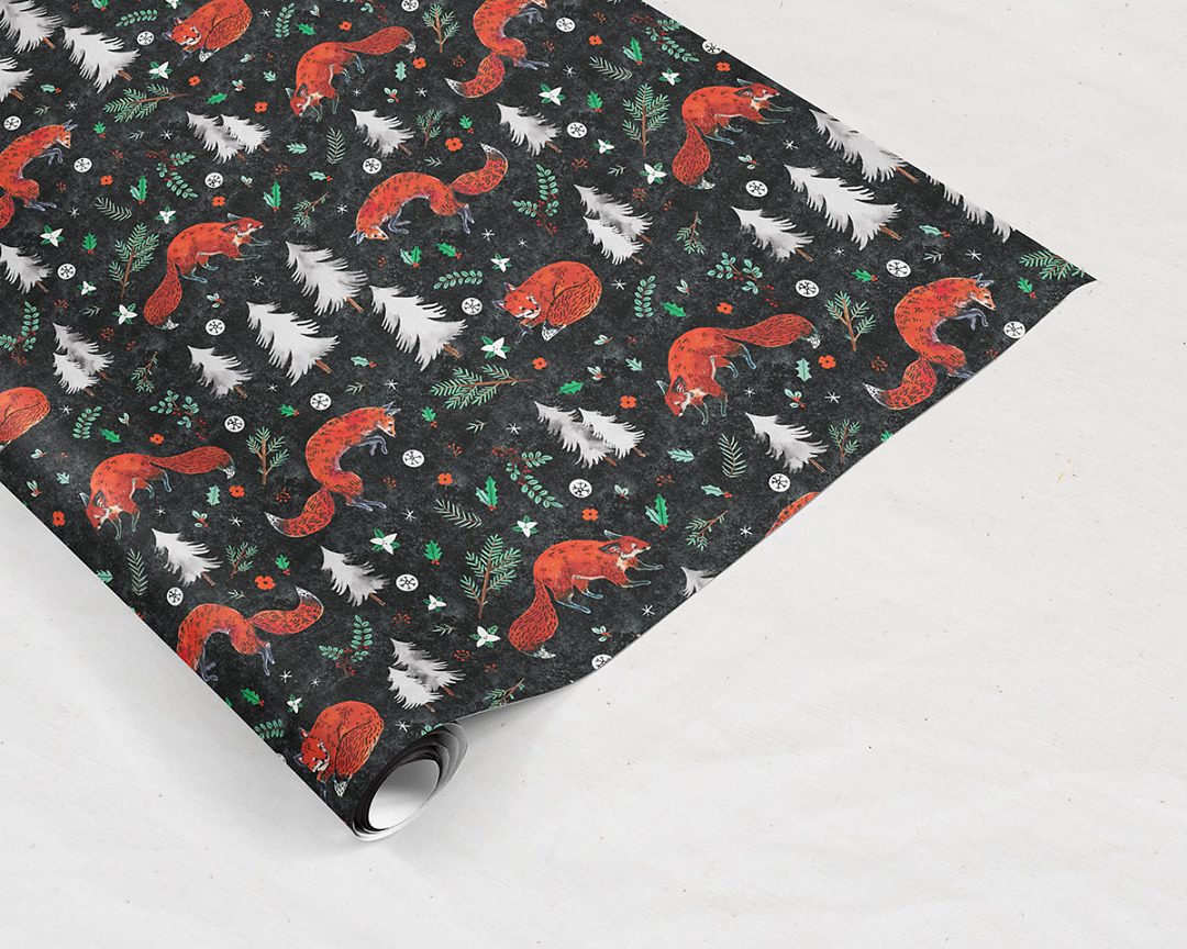 tilted wrapping paper sheet of Wildship Studio holiday gift wrap with fox, pine trees, snowflakes, poinsettia, and holly