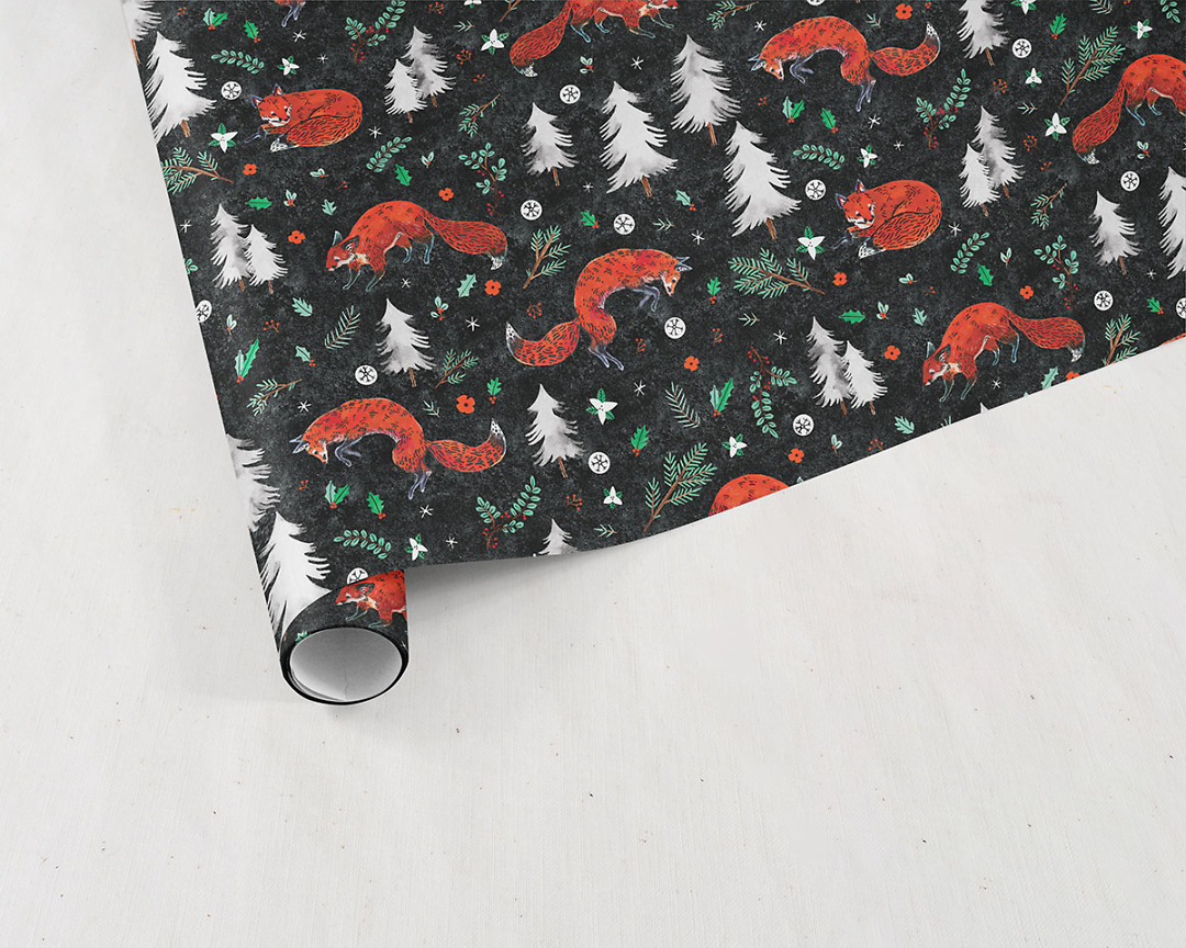 partially unrolled sheet of Wildship Studio holiday gift wrapping paper with fox, pine trees, snowflakes, poinsettia, and holly