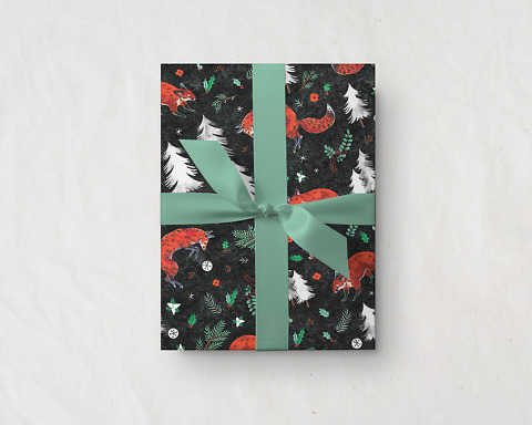 present tied with a green ribbon wrapped up in Wildship Studio holiday gift wrapping paper with fox, pine trees, snowflakes, poinsettia, and holly
